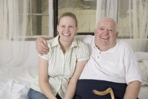 Adult daughter smiling sitting with elderly father
