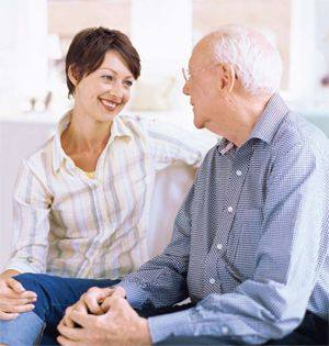 Adult daughter smiling and sitting on couch with elderly father