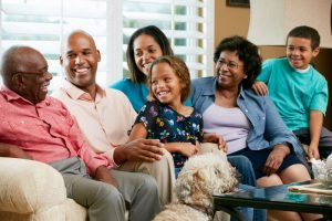 Family sitting around elderly man smiling