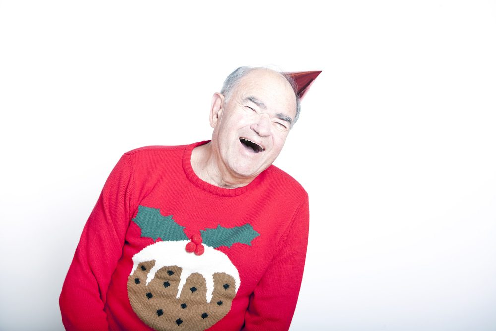 Elderly man in festive sweater and party hat laughing
