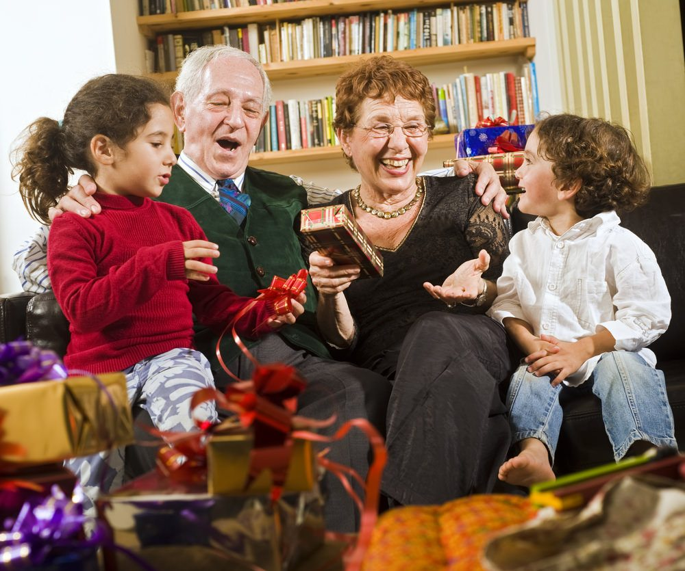 Grandparents opening gifts with grandchildren on couch